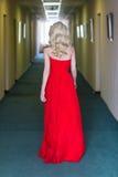 Blonde vorbildliche Frau der Schönheit, wenn rotes Kleid geglättet wird Stockfoto
