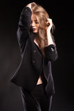 Blonde vorbildliche Frau, die in Mode Art auf schwarzem Hintergrund aufwirft Lizenzfreies Stockfoto