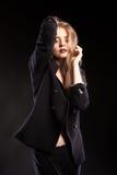 Blonde vorbildliche Frau, die in Mode Art auf schwarzem Hintergrund aufwirft Stockfoto