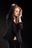 Blonde vorbildliche Frau, die in Mode Art auf schwarzem Hintergrund aufwirft Lizenzfreie Stockfotografie
