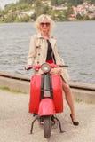 Blonde vorbildliche tragende Sonnenbrille auf einem Roller Stockfoto