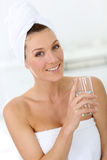 Blonde vrouw in badkamers drinkwater royalty-vrije stock foto