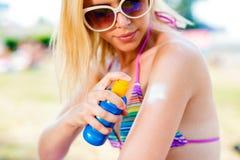 Blonde vrouw in bikini en zonnebril die op zonnescherm zetten Stock Afbeeldingen