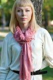 Blonde vrouw dichtbij boom Stock Afbeelding
