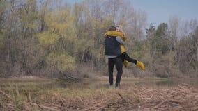 Blonde vrouw die aan de gebaarde knappe man en de sprong bij zijn omhelzingen lopen Verbazende mening van rivier en bosrest van j stock footage