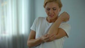 Blonde vrouw die aan elleboogpijn lijden, die haar pijnlijke wapen, verwonding en klem houden stock video