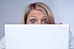 Blonde Vrouw die achter Laptop kijkt Stock Afbeelding