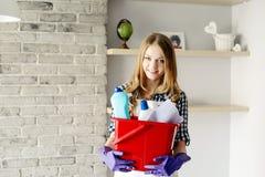 Blonde vrouw die een emmerhoogtepunt van reinigingsmachines houden Stock Afbeelding