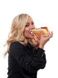 Blonde vrouw die een sandwich eten Stock Afbeelding