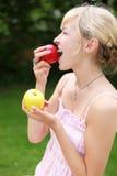 Blonde vrouw die een verse rode appel eten royalty-vrije stock foto's