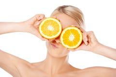 Blonde vrouw die glazen met sinaasappel maken halfs Stock Afbeeldingen