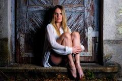 Blonde vrouw die in hete broek voor een doorstane deur zitten Royalty-vrije Stock Foto's