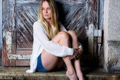 Blonde vrouw die in hete broek voor een doorstane deur zitten Stock Fotografie