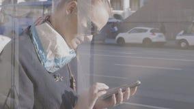 Blonde vrouw die mobiele telefoon met behulp van tegen glasbezinning van mensen die zich langs de straat bewegen stock video
