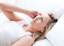 Blonde vrouw die op telefoon spreekt die op een bed ligt Stock Foto's