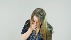 Blonde vrouw die op witte achtergrond niezen stock fotografie