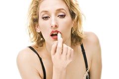 Blonde vrouw die rode lippenstiftmake-up zet Stock Foto's