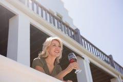 Blonde vrouw die rood wijnglas in balkon houden bij restaurant Stock Fotografie