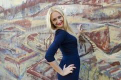 Blonde Vrouw die zich dichtbij het beeld met geschilderd grafiet bevinden Stock Afbeeldingen
