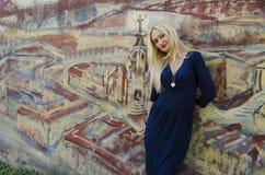 Blonde Vrouw die zich dichtbij het beeld met geschilderd grafiet bevinden Royalty-vrije Stock Foto