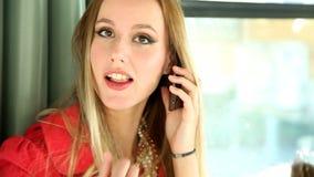 Blonde vrouw die zich in tram bevinden, op de telefoon spreken en aan de camera kijken stock video