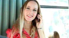 Blonde vrouw die zich in tram bevinden, op de telefoon spreken en aan de camera kijken stock footage