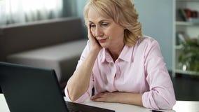 Blonde vrouw gevoel bored het letten op online video op middelbare leeftijd, die in slaap vallen royalty-vrije stock afbeelding