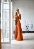 Blonde vrouw in lange kleding dichtbij de treden Stock Foto
