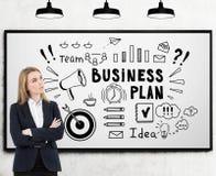 Blonde vrouw met gekruiste handen en een schets van het businessplan Stock Fotografie