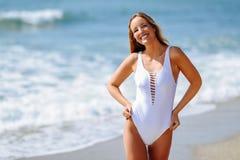 Blonde vrouw met mooi lichaam in swimswit op een tropisch strand royalty-vrije stock afbeeldingen