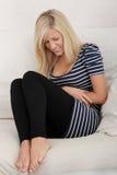 Blonde vrouw met stomachekwesties Stock Fotografie
