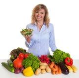 Blonde vrouw met verse groenten en groene salade Royalty-vrije Stock Fotografie