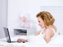 Blonde vrouw op een bed dat laptop met behulp van royalty-vrije stock fotografie