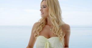 Blonde Vrouw op Oceaanfront balcony looking aan Kant stock videobeelden