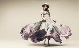 Blonde vrouw in purpere fladderende kleding en hoed royalty-vrije stock afbeelding