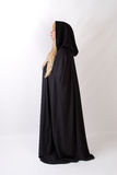 Blonde vrouw in zwart mantel zijaanzicht met een kap Stock Fotografie