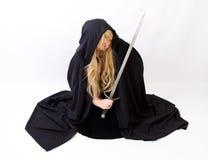Blonde vrouw in zwarte mantel met een kap met zwaard Royalty-vrije Stock Afbeelding