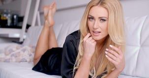Blonde Vrouw in Zwarte Nachthemden die op Laag liggen stock video