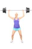 Blonde vrouwelijke atleet die een zware barbell opheffen Stock Foto