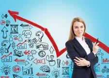 Blonde vrouwen en bedrijfspictogrammen op blauwe muur Royalty-vrije Stock Afbeeldingen