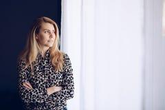 Blonde vrouwenjongelui door venster royalty-vrije stock afbeelding