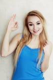 Blonde vrouwentiener die het o.k. teken van de succeshand tonen Stock Foto's