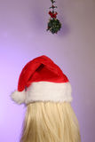 Blonde waiting for kiss. Waiting under mistletoe for a Christmas kiss is a blonde in a santa hat Stock Photo