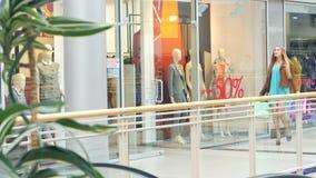 Blonde walks around the glass shop windows. Blonde with shopping bags around  walks around the glass shop windows stock video