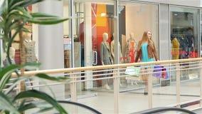 Blonde walks around the glass shop windows. Slow. Blonde with shopping bags around  walks around the glass shop windows, Slow motion stock video