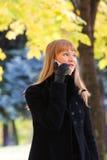 Blonde walks and talks on phone Stock Photos