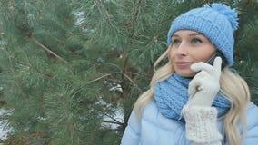 Blonde in warme klerenbesprekingen op de telefoon bij de sparrenachtergrond stock footage