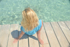 Blonde with wavy hair on the shore of the turquoise sea Stock Photo