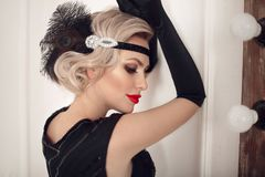 Blonde wavy hairstyle. Elegant woman portrait in retro style. Beautiful girl wears in vintage black dress and gloves. Hollywood. Red lips makeup stock images