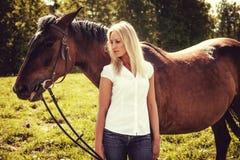 Blonde weibliche Aufstellung mit braunen Pferden auf einem Gebiet Lizenzfreies Stockfoto